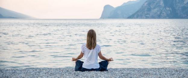 Pessoa meditando de frente ao lago
