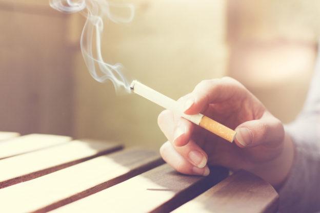 Mão segurando um cigarro aceso