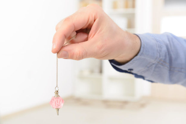 mão segurando um pêndulo