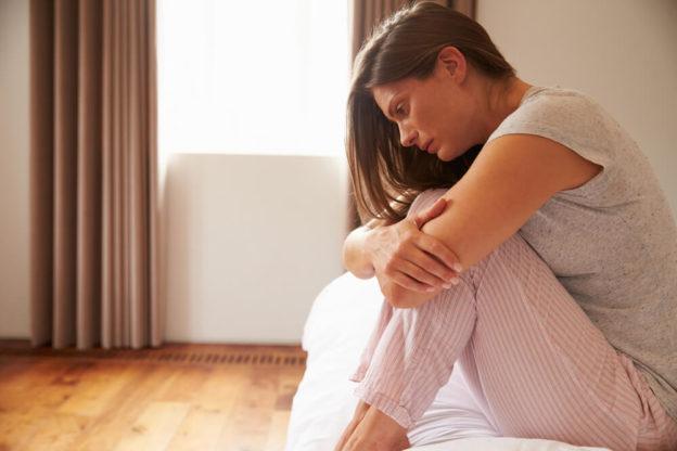 Mulher chorando em cima da cama