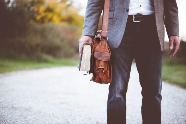 Imagem de um homem com uma bolsa e um livro em uma estrada