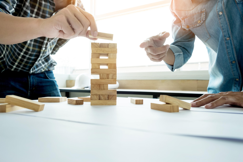 Mãos de duas pessoas escolhendo quais peças remover no jogo jenga
