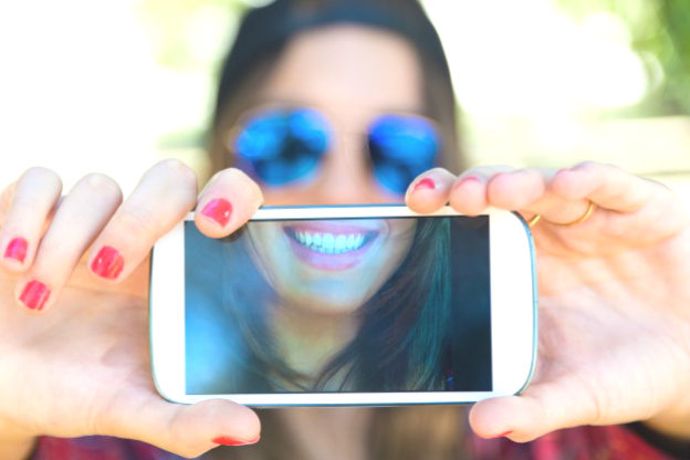 portrait-of-beautiful-girl-taking-a-selfie-with-mobile-phone-in_1301-3497